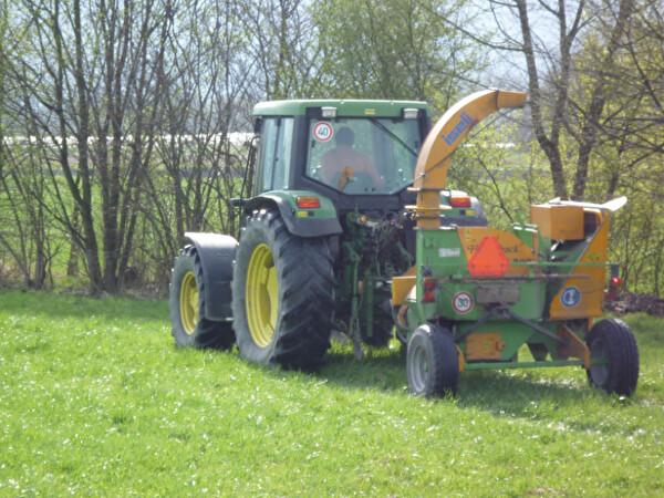 ein Traktor woran eine Häckslermaschine ist