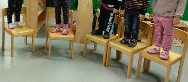 Spielgruppenkinder stehen auf den Stühlen