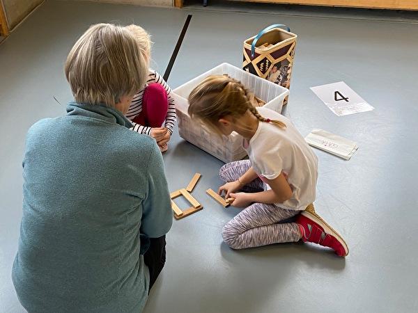 Senioren unterstützen im Unterricht, sie Bauen mit Holzsteinen einen Turm
