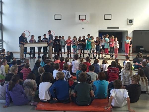 Lehrpersonen und die 1. Klasse eröffnen das Schuljahr