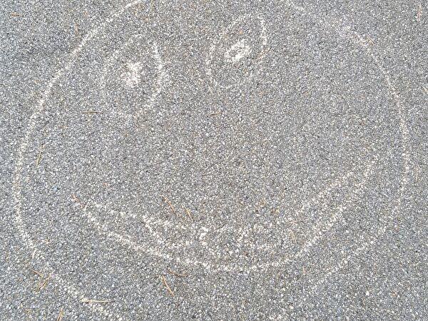 Smiley mit Kreide auf Asphalt