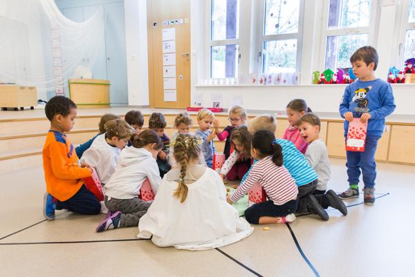 Kindergartenkinder knien am Boden im Kreis und spielen, einige Kinder sind verkleidet