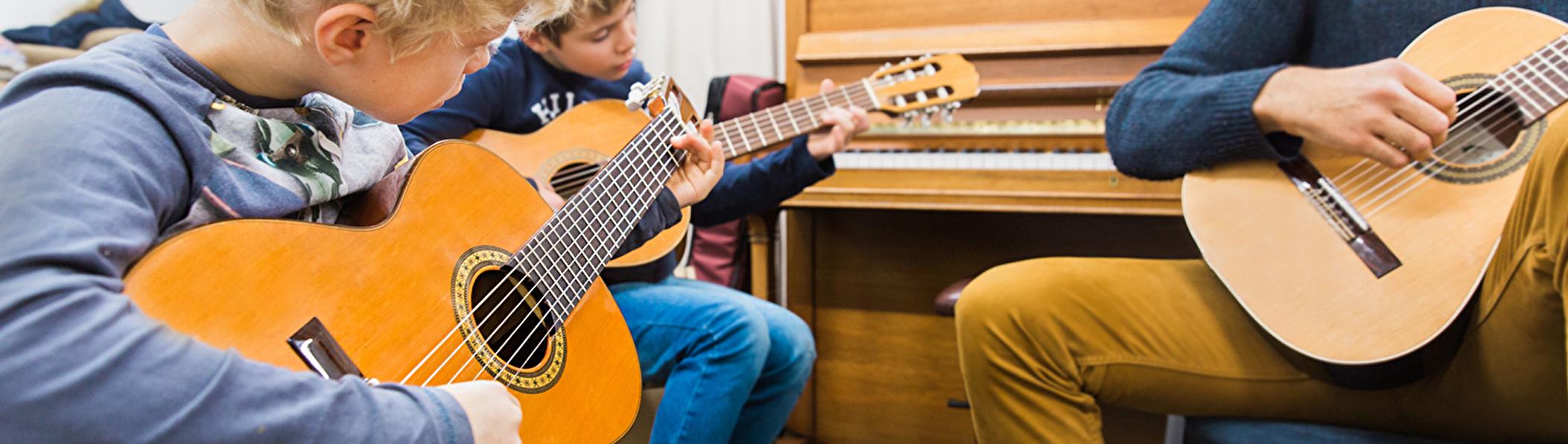 zwei Kinder am Gitarre spielen, begleitet vom Gitarren Lehrer