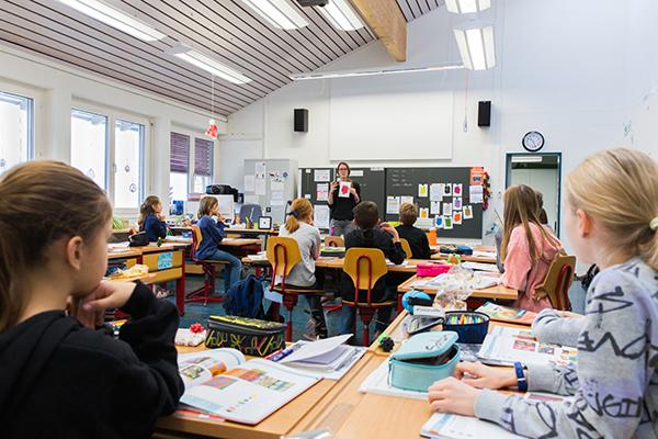 Klasse von hinten, Schüler sitzen in den Bänken, Lehrperson erklärt einen Auftrag