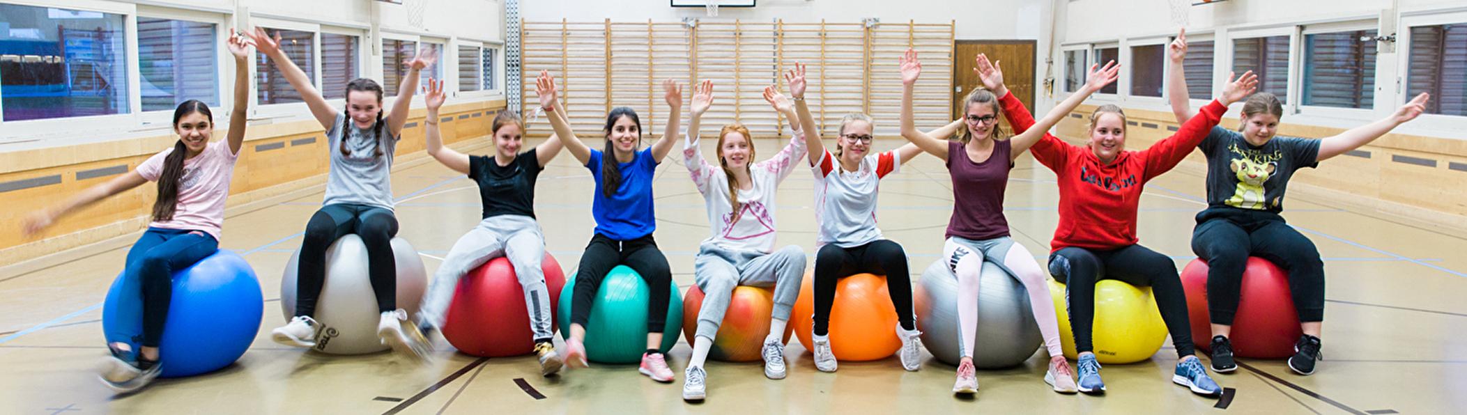 Mädchen sitzen auf Gymnastikbällen und halten die Hände in die Höhe