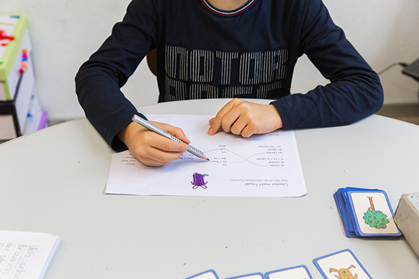 Junge am Hausaufgabenblatt lösen