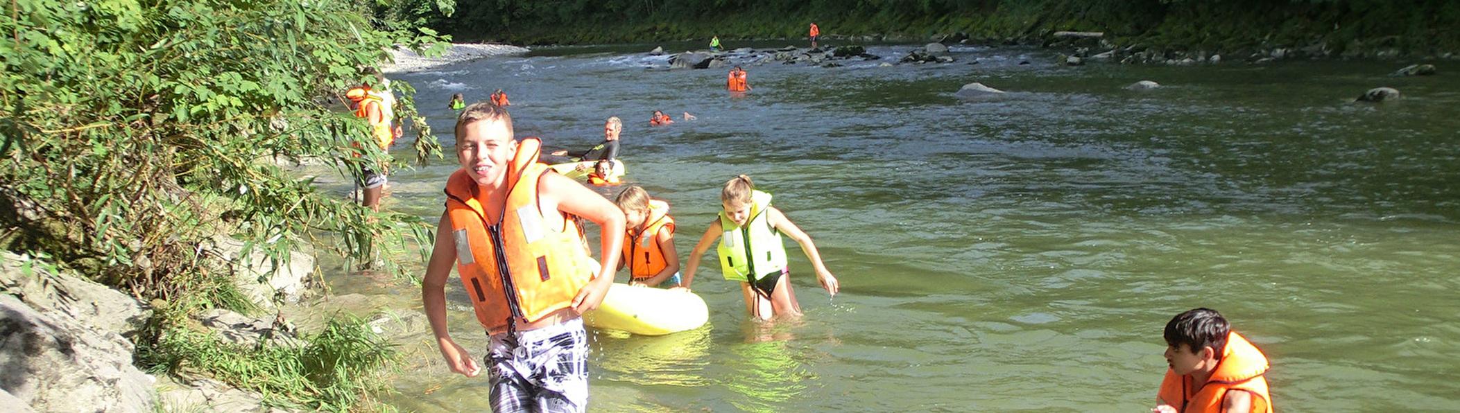 Schulklasse am Baden mit Schwimmwesten uns Schwimmring