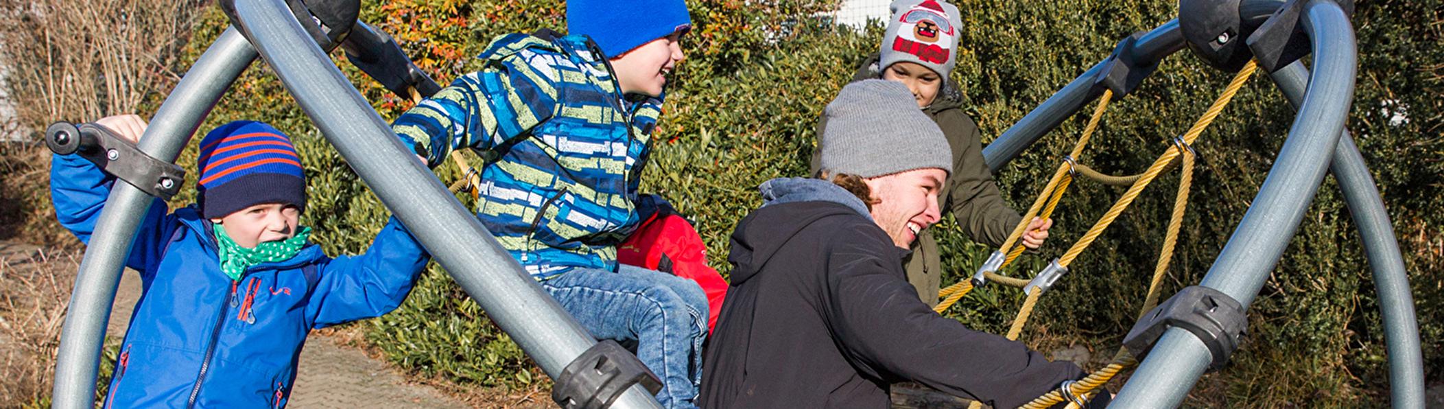 Zivildienstleistender mit Kindern auf dem Klettergerüst