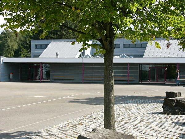Das Schulhaus Gschwader steht am Stadtrand und hat einen schönen Ausblick auf Wiese und Waldrand.