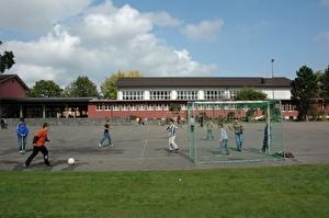 Schulhaus Pünt mit Pausenplatz, hinten die Turnhalle