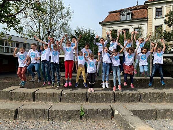 Das ist ein Foto der 3. Klasse von Rahel Brunschwiler. Die Kinder springen vor Freude in die Luft.