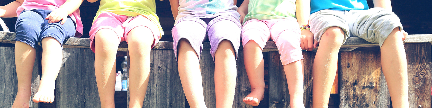 Kinder sitzen auf Zaun