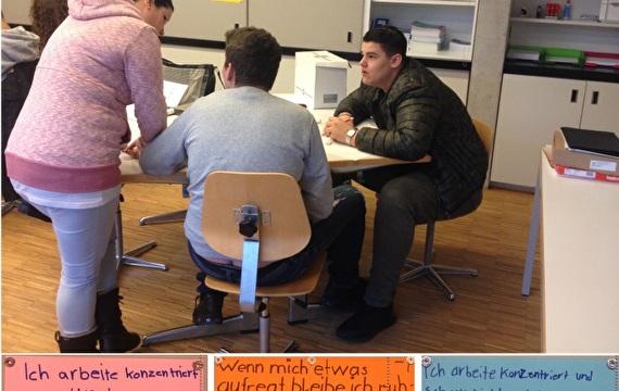Lehrperson bespricht Aufgaben mit Schülern