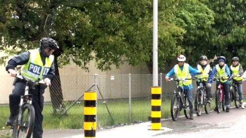 Schulkinder auf Velos mit Polizist
